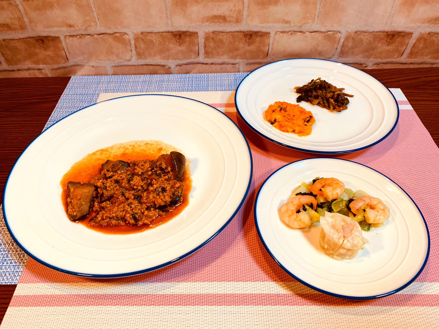 (メニューの一例)麻婆茄子、しゅうまいと海鮮炒め、カボチャの和え物、菜の花とぜんまいのナムル