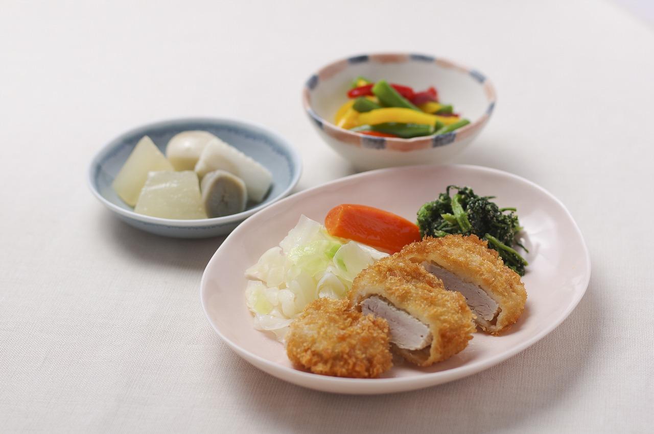 (メニューの一例)ひれかつ、いかと里芋の煮付け、彩り野菜の洋風炒め、春菊の胡麻和え。ひれかつは厚みのあるボリューム感を大切にしながら柔らかく仕上げ、彩り豊かな副菜で食欲がわくよう工夫しました。